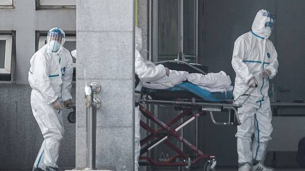 Image: Medical staff members carry a patient into the Jinyintan hospital, w