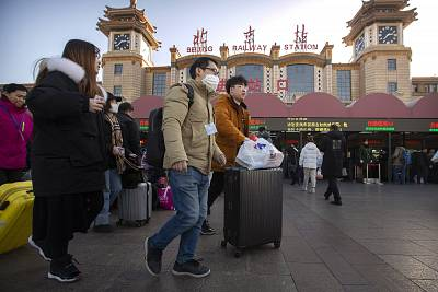 A traveler wears a face mask as he walks outside Beijing Railway Station on Monday.