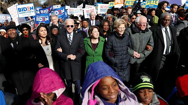 Image: Seven of the democratic U.S. 2020 presidential candidates walk arm-i