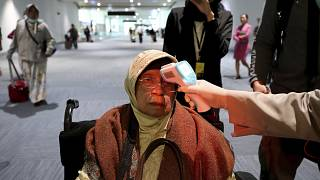 Image: A health official scans the body temperature of a passenger as she a