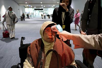 A health official scans the body temperature of a passenger as she arrives at the Soekarno-Hatta International Airport in Tangerang, Indonesia, on Wednesday.
