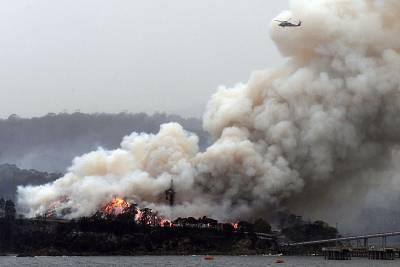 A military helicopter flies above a burning woodchip mill in Eden, in Australia\'s New South Wales state on Jan. 6, 2020.