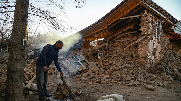 A villager stands by his collapsed house after an earthquake in Sivrice, ne