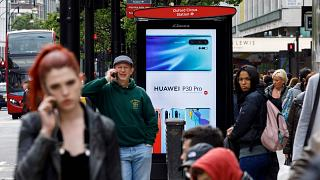 Image: Pedestrians use their mobile phones near a Huawei advert at a bus st