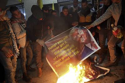Palestinians burn a poster showing President Donald Trump as they protest the American peace plan in Bethlehem on Monday.