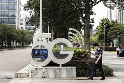 An employee using a smartphone walks past a signage for the 5G Park at the Huawei Technologies Co. headquarters in Shenzhen, China, on May 22, 2019.