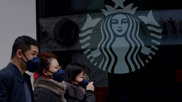 Image: People wearing protective face masks walk past a closed Starbucks co