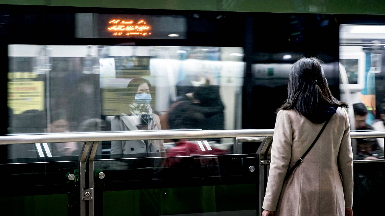 Image: A woman wears a protective mask while waiting for the subway in the
