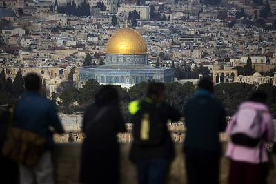 Tourists look out from the Mount of Olives at a view of Jerusalem\'s Old City on Tuesday.
