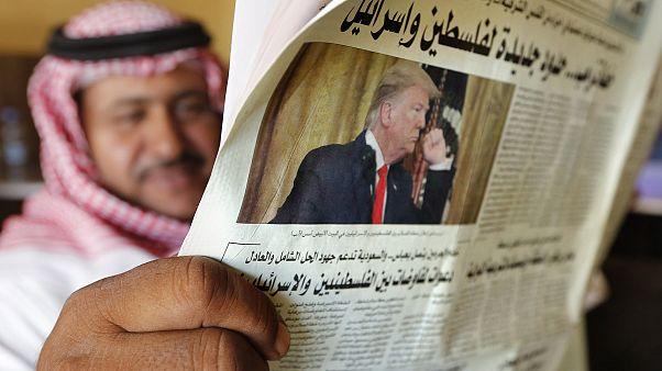 Image: A man holds the daily Asharq Al-Awsat newspaper
