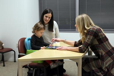Katie Harbison watches as her daughter, 22-month-old Maggie Harbison, plays on a tablet with clinical research assistant Sarah Corrigan at Seattle Children\'s Research Institute.