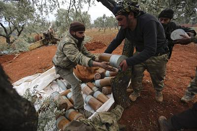 Syrian rebel fighters prepare to fire at government positions in Idlib province, Syria on Thursday.