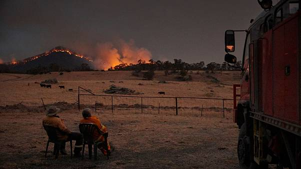 Image: Rural Fire Service volunteer firefighters watching as the New South