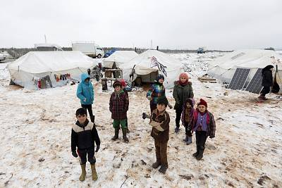 Internally displaced children stand on snow near tents at a makeshift camp in Azaz, Syria on Thursday.