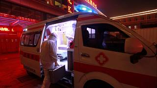 Image: A medical worker in protective suit gets onto an ambulance at a hosp