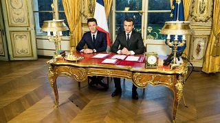 Image: French President Emmanuel Macron delivers a speech next to then spok