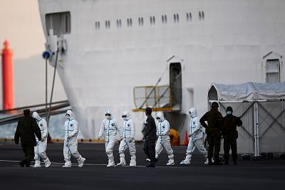 People wearing protective suits walk from the Diamond Princess cruise ship, with around 3,700 people quarantined onboard due to fears of the new coronavirus, at the Daikoku Pier Cruise Terminal in Yokohama port on Feb. 10, 2020.