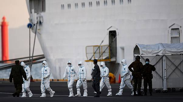 Image: People wearing protective suits walk from the Diamond Princess cruis