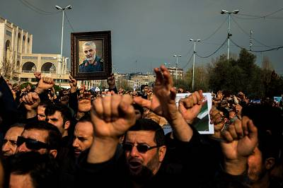 Protesters hold a photo of Iranian General Qassem Soleimani during a demonstration in Tehran on Jan. 3, 2020.