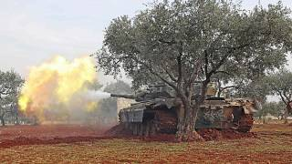 Image: Syrian rebel fighters fire from their position in the countryside of