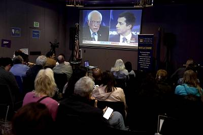 As Sen. Bernie Sanders, I-Vt., and Pete Buttigieg are seen on a screen, people participate in a Democratic presidential primary debate watch party at Las Vegas LGBT Center on Wednesday night.