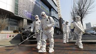 Image: Workers wearing protective gears spray disinfectant against the new