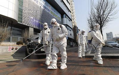 Workers wearing protective gear spray disinfectant in front of a church in Daegu, South Korea, on Thursday.