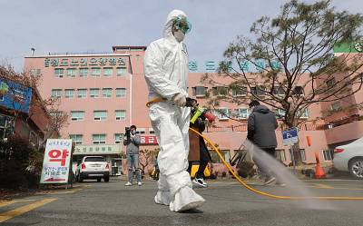 A South Korean health official sprays disinfectant in front of a hospital where a total of 16 infections have now been identified with the coronavirus, near the southeastern city of Daegu on Feb. 21.