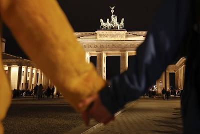 People hold hands as they form a human chain, during a vigil for victims of last night\'s shooting in the central German town Hanau, at the Brandenburg Gate in Berlin, Germany, Thursday, Feb. 20.
