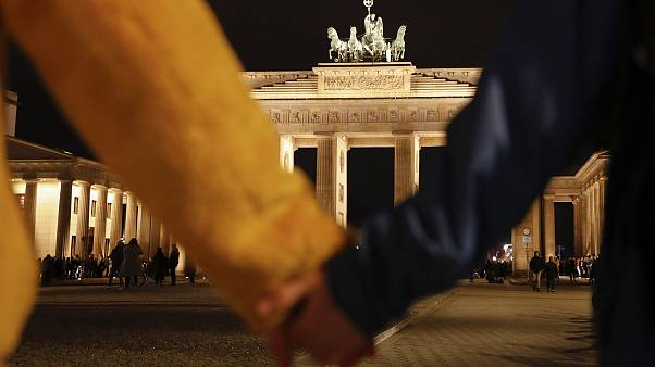 Image: People hold hands as they form a human chain, during a vigil for vic