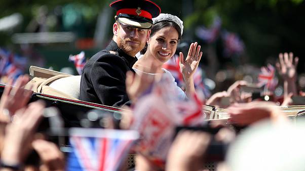 Image: Prince Harry and Meghan, Duchess of Sussex, wave from their carriage
