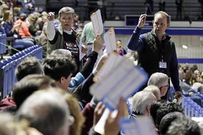 Caucusgoers seated in the section for Joe Biden hold up their first votes as they are counted a on the Drake University campus in Des Moines, Iowa, Feb. 3, 2020.