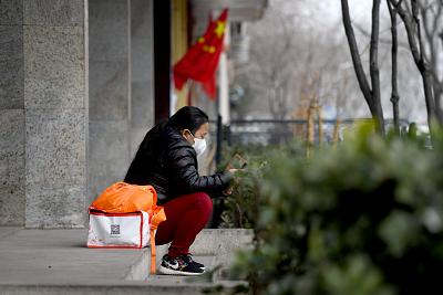 A woman wears a face mask as a preventive measure against the COVID-19 coronavirus near the entrance of the Peking University People\'s Hospital in Beijing on Friday.