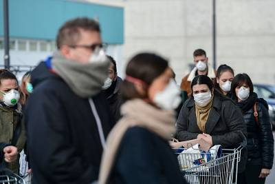 Residents wearing respiratory masks wait to go into a supermarket in small groups of forty people on Sunday in the small Italian town of Casalpusterlengo.