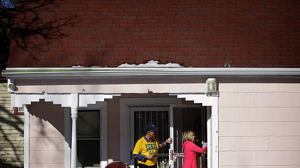 Image: Len Edgerly and Darlene Determan knock on a door while canvasing for