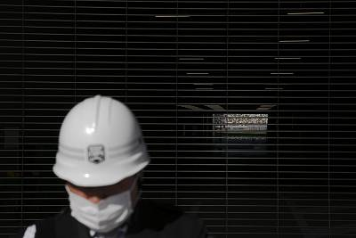 A security guard with a mask stands in front of a tunnel leading to the field of the New National Stadium, a venue for the opening and closing ceremonies at the Tokyo 2020 Olympics, Sunday, Feb. 23, 2020, in Tokyo.
