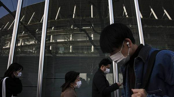 Image: People with masks walk past a building reflecting the New National S