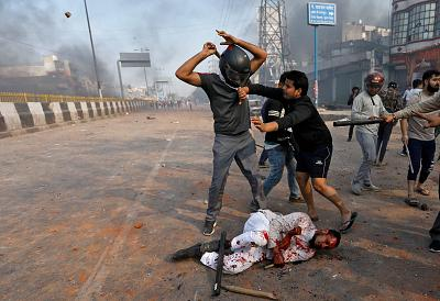 A Muslim is beaten by people supporting a new citizenship law beat in New Delhi on Monday.