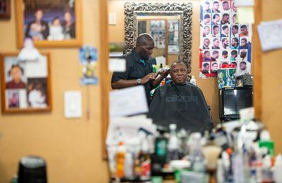 Barber Anderson J. Washington with veteran Charles Peaks at CJ\'s Barbershop.