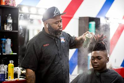 Barbershop owner ReCarlo Lewis sprays his client\'s hair at Lucciono\'s in North Charleston, S.C. on Feb. 26, 2020.