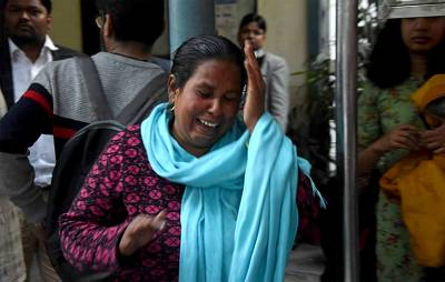 A woman sobs at the sight of her husband, who was shot in the face while sitting outside his home on Tuesday, Feb. 25.
