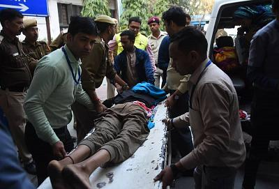 A teenager is taken to hospital after being shot in the waist in Kardam Puri, New Delhi on Tuesday, Feb. 25.
