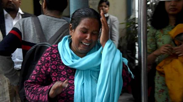 Image: A woman sobs at the sight of her husband, who was shot in the face w