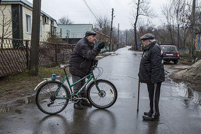 Vasyl Tsarenko, left, and Vitalii Maksiuk discuss the protests in their town in Novi Sanzhary, Ukraine, on Feb. 24, 2020.