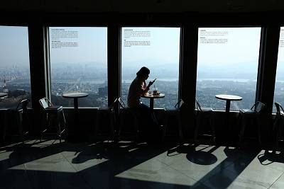 A woman sits at an empty cafe in a tower in Seoul, South Korea on Monday.