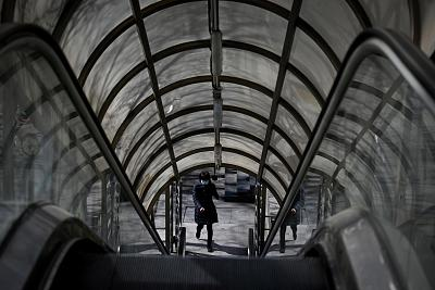A woman wearing a face mask uses an escalator in Beijing on Tuesday.