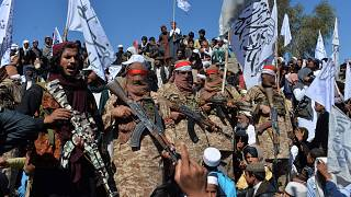 Image: Afghan Taliban militants and villagers attend a gathering as they ce