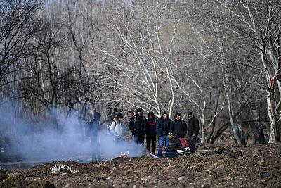 Migrants keep warm as they gather near the Tunca river waiting to resume their efforts to enter Europe in Edirne.