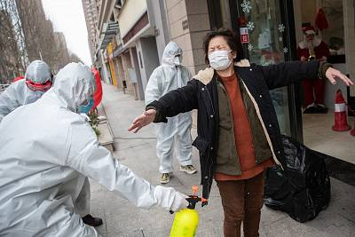 A woman who has recovered from the coronavirus infection, is disinfected by volunteers as she arrives at a hotel for a 14-day quarantine after being discharged from a hospital in Wuhan on Sunday.