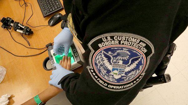 Image: A woman who is seeking asylum has her fingerprints taken by a U.S. C